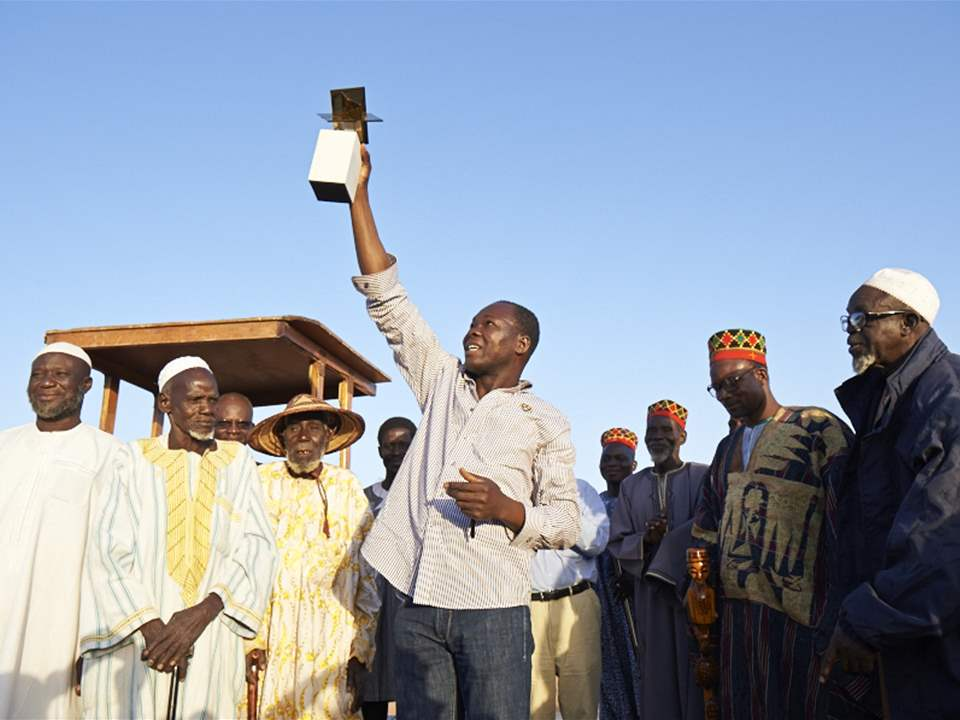 Raising the standard: Diébédo Francis Kéré (center) and representatives of the local village, …