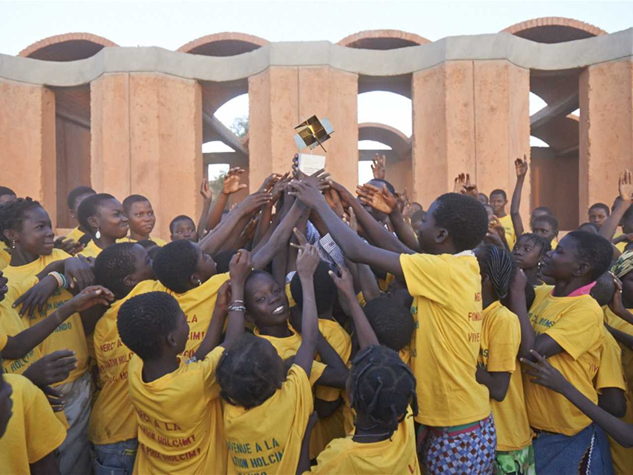 """Vive le prix Holcim"": enthusiastic students raise the Global Holcim Awards Gold trophy in …"